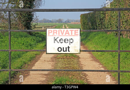 A Private Keep Out sign on a locked gate on a track leading over farmland at Freethorpe, Norfolk, England, United Kingdom, Europe. - Stock Image