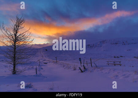 Evening sun catches the clouds after a storm over the snow-covered interior of Iceland - Stock Image