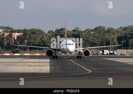 Jet plane following yellow centerline while taxiing on airport taxiway path, illustrating the highly regulated nature of modern commercial aviation - Stock Image