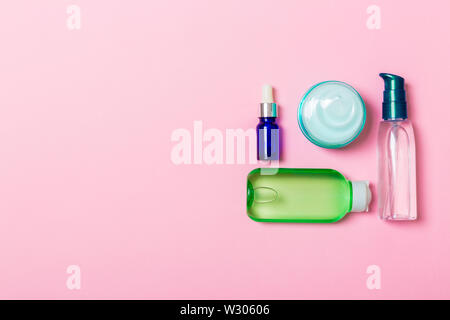 Cosmetics SPA branding mock-up, top view with copy space. set of tubes and jars of cream flat lay on pink background. - Stock Image