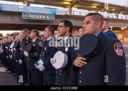 Merrick, New York, USA. 11th September 2015. Firefighters from Merrick and New York City stand in line and hold - Stock Image