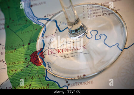 Bordeaux French wine 'route du vin' tasting concept, with wine glass stem, in close up, on old historic Bordeaux wine producing areas map France - Stock Image
