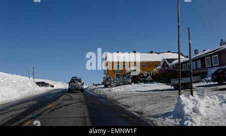 Car driving Eastbound on road E7 over Hardangervidda, passing Dyranut, Norway, with high walls of snow surrounding - Stock Image