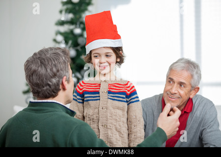Father And Grandfather Looking At Son During Christmas - Stock Image