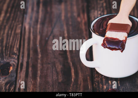 BBQ brush with barbecue sauce on the tip resting on a white cup over a rustic wood background with drop on table. Extreme shallow depth of field with  - Stock Image