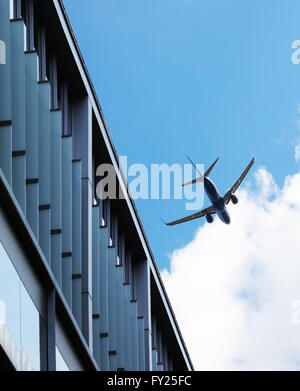 Aircraft flying over building - Stock Image