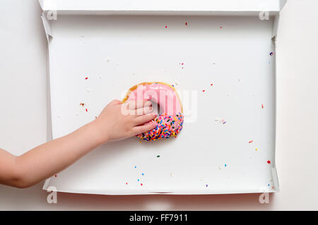 Donut box with a young female child's hand reaching to grab the last pink strawberry frosted doughnut - Stock Image