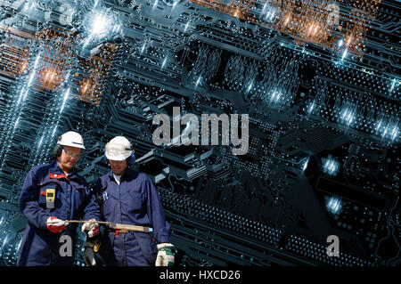 two hi tech technicians with a futuristic large computers motherboard in background - Stock Image