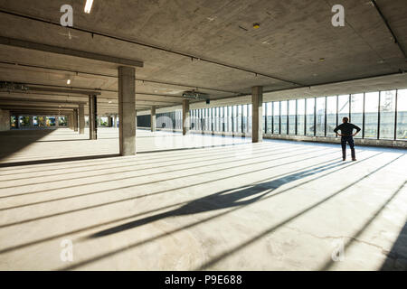 Single businessman exploring new empty raw business space for a new office, light streaming in large windows. - Stock Image