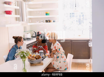 Young women friends enjoying breakfast at dining table - Stock Image