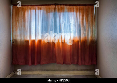 Empty bedroom in a high-rise apartment block with orange net curtains. - Stock Image