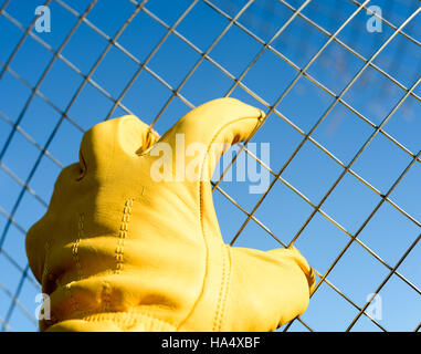 Yellow leather gloved male hand grabs wire mesh wire against a blue sky background. Copyspace area for construction - Stock Image