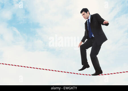Stock image of businessman walking the tightrope - Stock Image