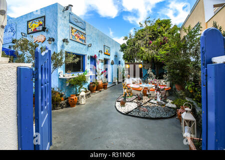 A colorful patio outside a souvenir shop and restaurant in the resort city of Thira on the island of Santorini, Greece. - Stock Image