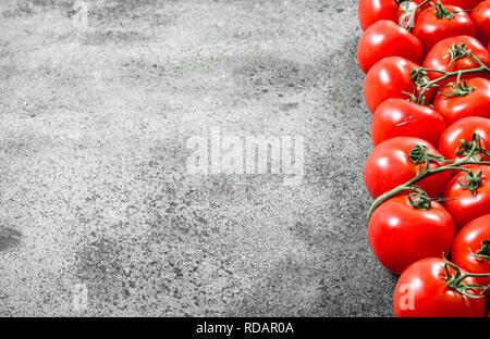 Fresh ripe tomatoes . On rustic background - Stock Image