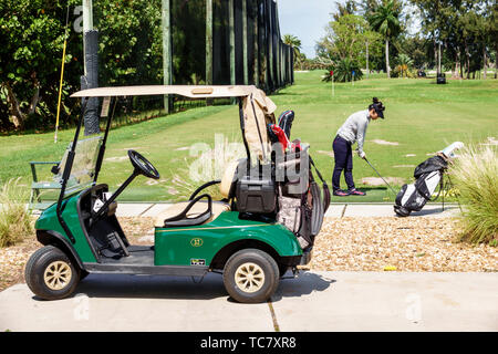 Miami Beach Florida Normandy Shores Public Golf Club Course practice driving range Asian woman golfer practicing swinging club playing electric cart - Stock Image