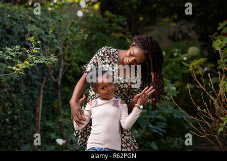 A mother and daughter standing together in a garden - Stock Image
