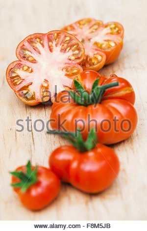 Whole and sliced Red Star tomatoes - Stock Image