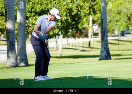 Miami Beach Florida Normandy Shores Public Golf Club Course man golfer swinging driver driving tee off - Stock Image