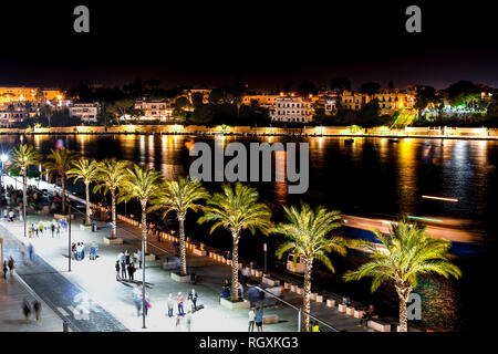 Tourists and locals enjoy a late night on the boardwalk promenade at the port of Brindisi in the Puglia region of Southern Italy. - Stock Image