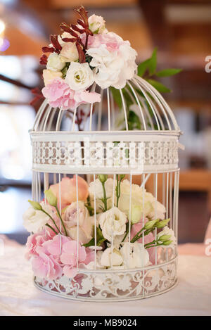 Wedding romantic decor for guests dinner tables or gifts and guestbook tables, with white vintage decorative birdcage filled with white roses - Stock Image