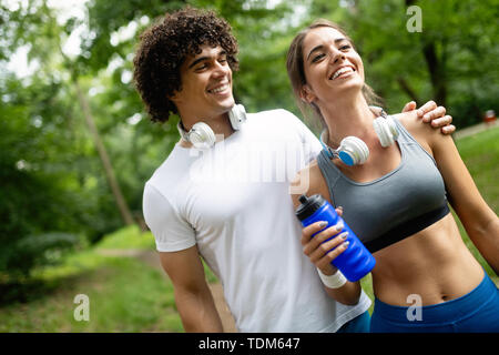 Athletic couple friend drinking water after running - Stock Image