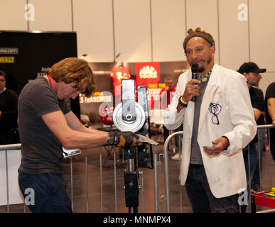 Racing driver Freddie Hunt learning how to using a wheel to shape a metal panel, assisted by Fuzz Townshend,  at the Car S.O.S. area, during the  London Motor Show 2018. - Stock Image