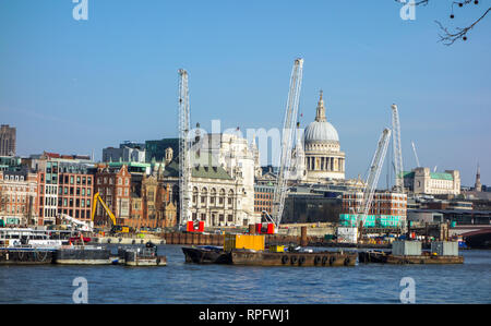 The London skyline seen from the south bank of the river Thames with cranes and a view of St Paul's cathedral - Stock Image