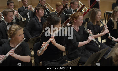 High angle view of student musicians playing flutes in orchestra recital - Stock Image