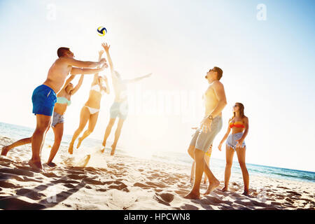 Group of friends is playing beach voleyball at sunset time - Stock Image