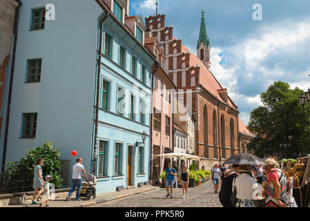 Riga Old Town, view of people walking in and looking at market stalls near  St John's Church in Skarnu Iela in the medieval center of Old Riga, Latvia. - Stock Image