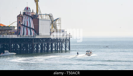 Brighton, UK. 19th Apr, 2019. A water skier heads around Brighton Palace Pier as visitors flock to the seaside to enjoy the Good Friday sunshine as temperatures reach the mid twenties along the South Coast Credit: Simon Dack/Alamy Live News - Stock Image