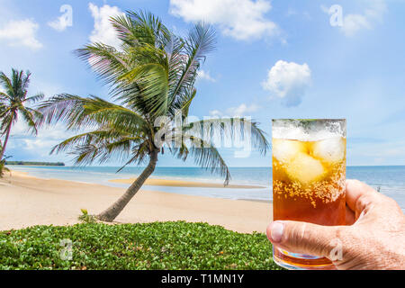 Hand holding a rum and coke cocktail in glass with ice on beach with coconut palm tree, Thailand - Stock Image