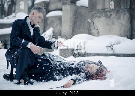 Duel of dark and light magicians with the help of magic wands on the snow background. Closeup. - Stock Image