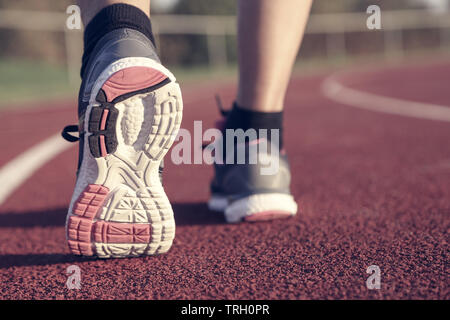 Woman running on athletic track at afternoon - Stock Image