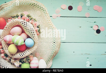 A beautiful and colorful close-up flat of easter eggs in plain pastel colors and striped in a basket with flowers and space - Stock Image