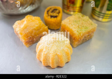 Special turkish dessert assortment with tea set. Kanafeh, baklava, Ma'amoul and Makroudh pastries - Stock Image