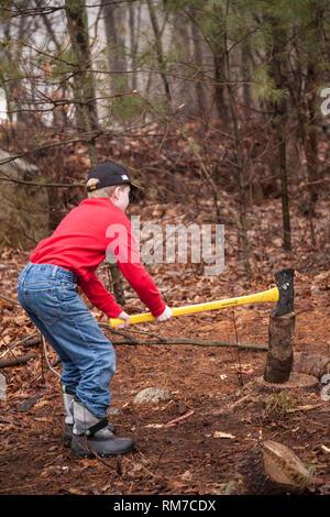 Young Boy Splitting Wood for Kindling, USA - Stock Image