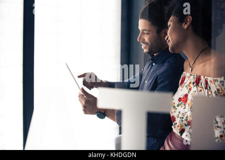 Couple looking at digital tablet together - Stock Image