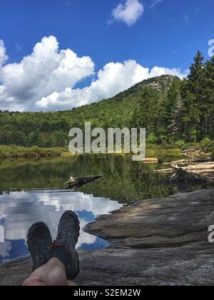 Hiker's Feet with boots in Adirondack Mountains by lake, New York, NY, USA - Stock Image