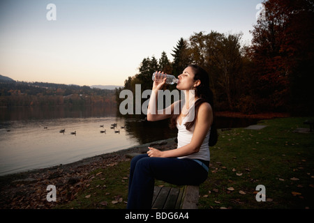 A young woman in fitness attire drinks water from a disposable water bottle next to a lake - Stock Image
