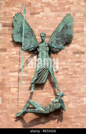 Coventry, UK - July 26th 2018: A sculpture on the exterior of Coventry Cathedral depicting St. Michaels victory over the Devil, in Coventry, UK. - Stock Image