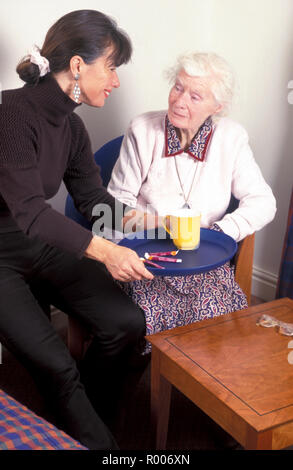 carer female adult bringing old lady tea on a tray - Stock Image