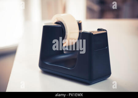 Black Sellotape Holder On A White Office Desk - Stock Image