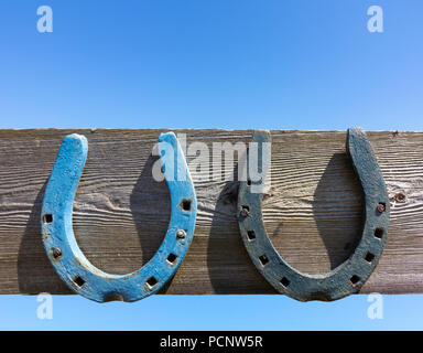 Two Horseshoes nailed to a gate against a blue sky - Stock Image