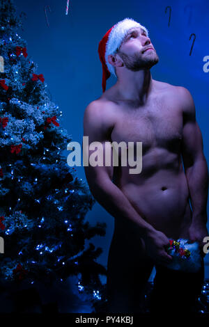 Hunky naked male santa wearing nothing but a hat holds stocking full of candy as his looks to the sky - Stock Image