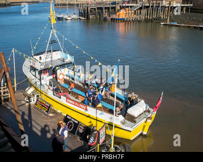 Passengers on Esk Belle lll  pleasure boat in Whitby Harbour on a sunny autumn day awaiting departure - Stock Image