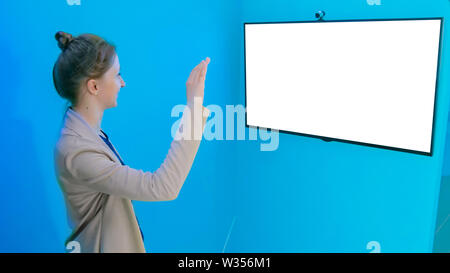 Woman using white empty interactive display - Stock Image