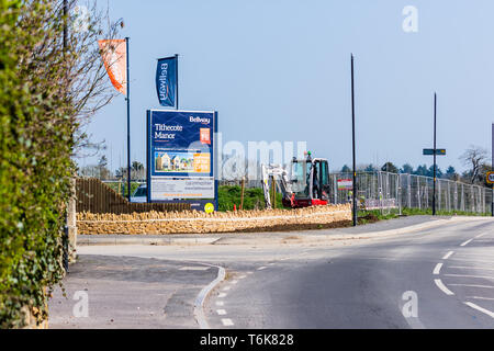 A sign flags of a new housing development Tithecote Manor by Bellway in Bradford on Avon Wiltshire with fencing a small digger next to the sign. - Stock Image