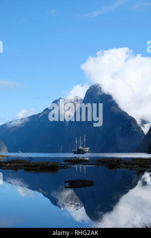 View over Milford Sound, New Zealand. Peaks reflected in fjord. - Stock Image